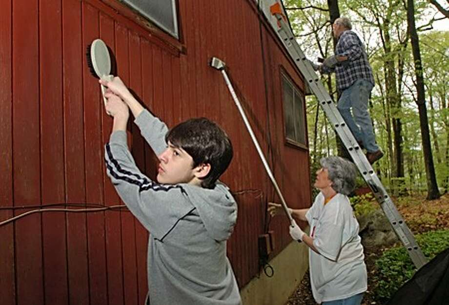 14 year old Domenick Gaspasso, Pat Olson and John Grant join other St. Jerome parishioners in refurbishing a home on Wake Robin Rd in Norwalk as part of the Americares Homefront program. Hour photo / Erik Trautmann
