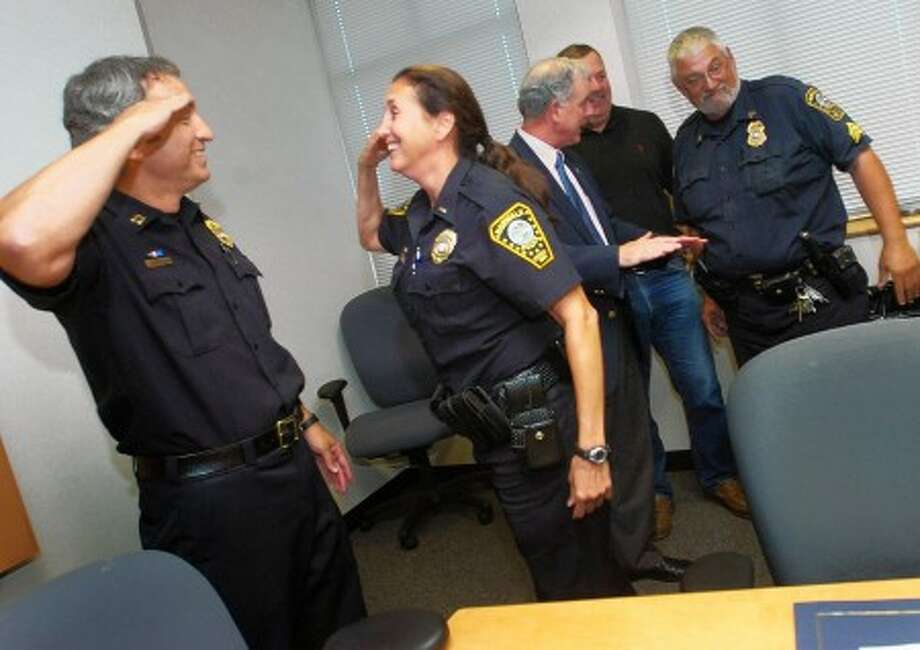 Retirees and husband and wife, Norwalk police Capt. Daniel Walsh and Lt. Angela Walsh salute each other for the last time while Police Commissioner Dan O''Connor chats with retirees Sgt. Ronald Pine and Sgt. Chuck Fallo during a farewell party at police Headquarters Tuesday. Hour photo / Eriok Trautmann