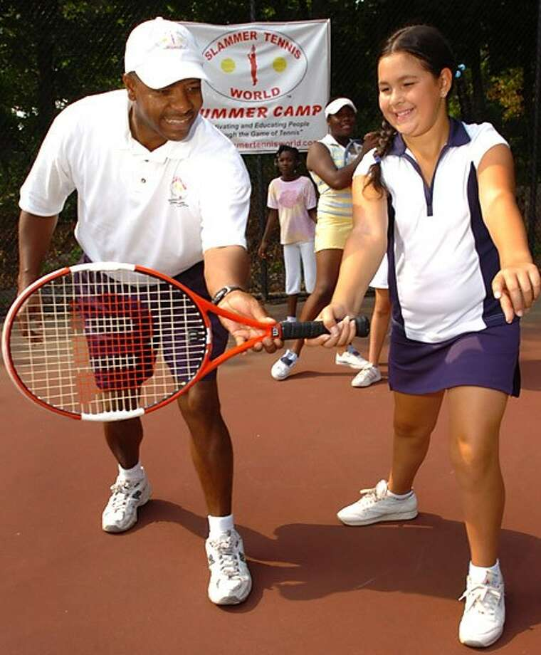 Founder of Slammer tennis World, Marvin Tyler, work with Marion Gardella, 10, on the last day of the camps summer program. The program offers two 3 week summer camps that instruct kids on the basic fundamentals and techniques of tennis. Hour photo / Erik Trautmann