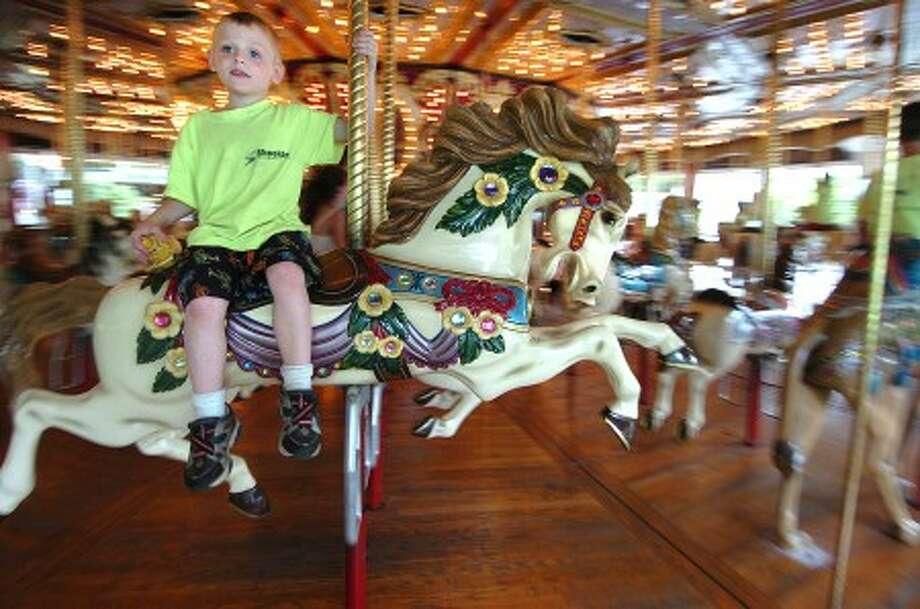 Photo/Alex von Kleydorff. 9 yr old Kody Prindel from Torrington. rides the carousel at Quassy.