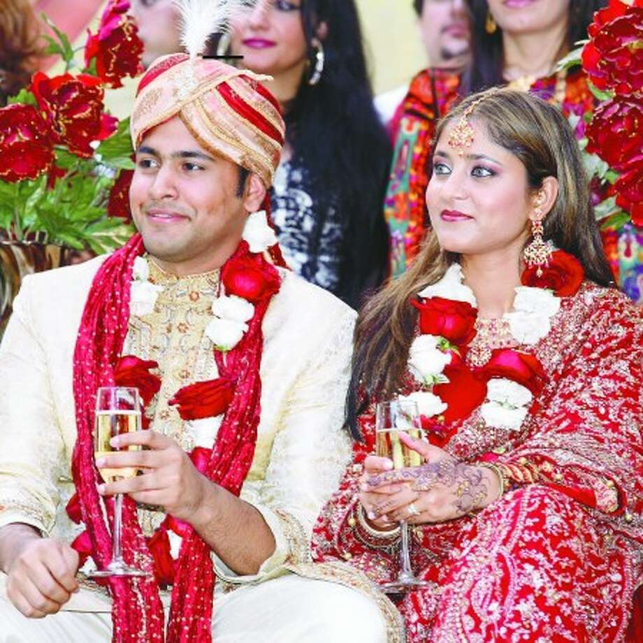 Aram Jawed and Sufia listen to a toast given at their wedding ceremony in Wilton. Photo by Danielle Robinson