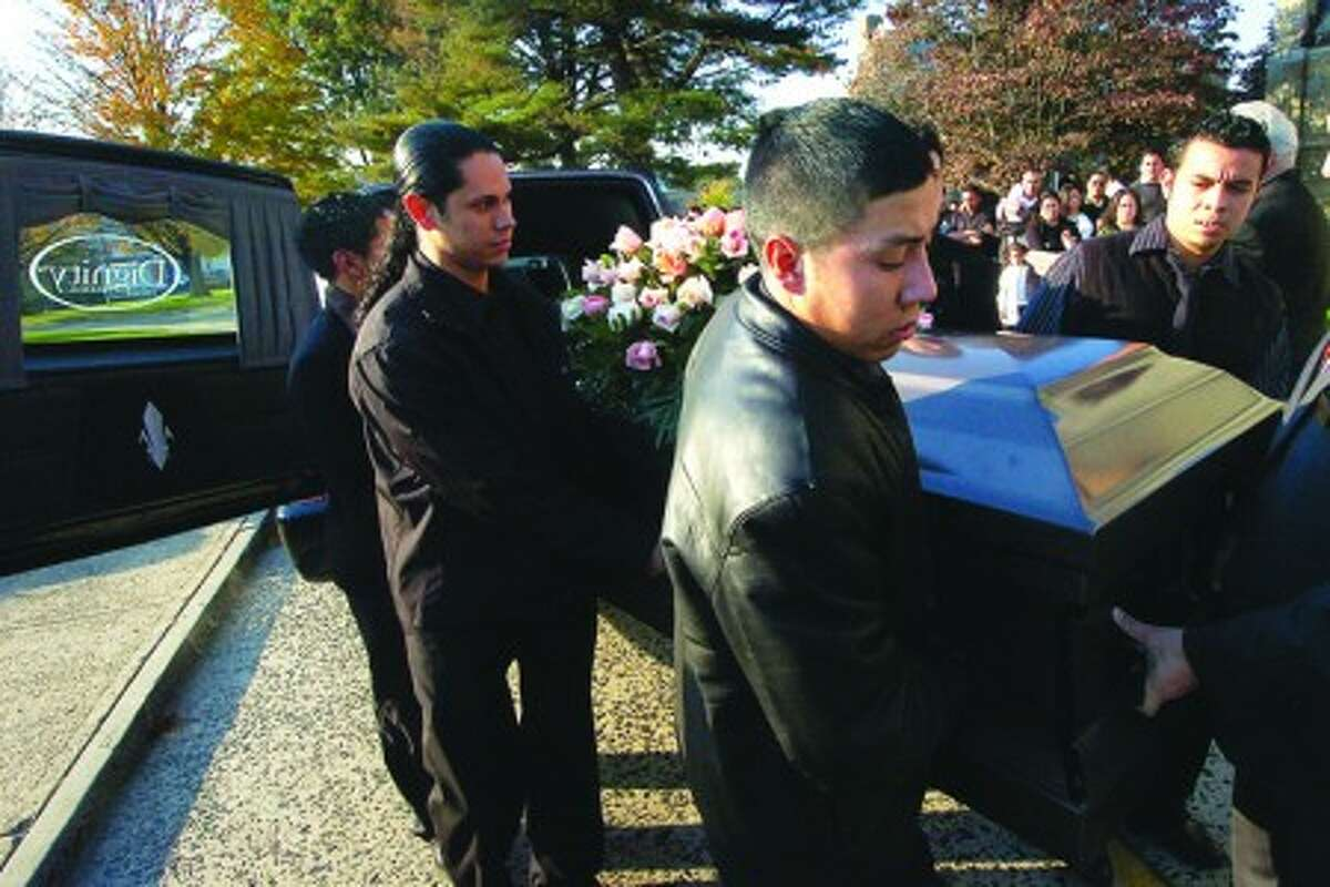 Photo/Alex von Kleydorff. Family and Friends carry the casket containing 33yr old Jose Morales into St Marys RC Church in Stamford. Morales was shot and killed during a robbery at Miracle Shell gas station in Norwalk last week