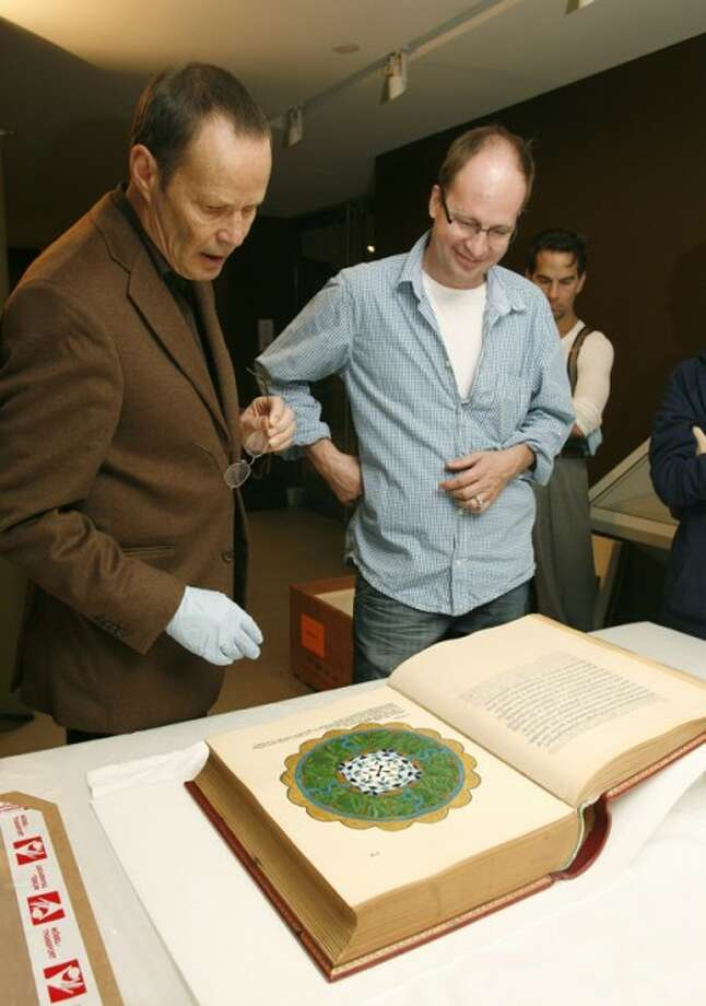 "In this photo provided by the Rubin Museum of Art, the museum''s chief curator, Martin Brauen, left, and Felix Walder, great-grandson to Carl Jung, inspect Carl Jung''s ""The Red Book"" after it''s arrival at the Rubin Museum of Art in New York Tuesday, Sept. 29, 2009. ""The Red Book,"" considered one of the most important unpublished works in the field of psychology, will be displayed to the public for the first time on October 7, coinciding with the first-ever publication of the book by W.W. Norton & Company. (AP Photo/Rubin Museum of Art, Stuart Ramson)"