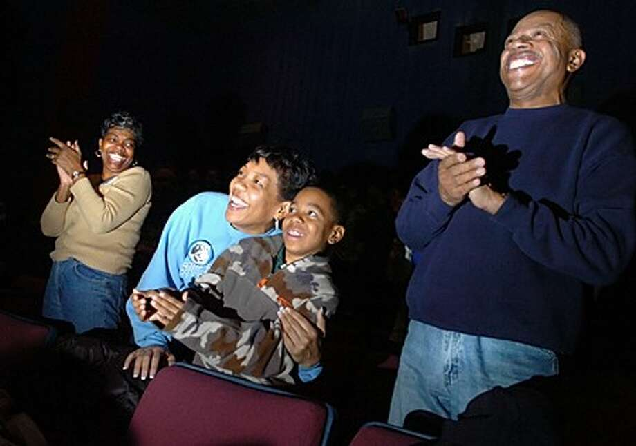 E.J. Dubois his son Bryce Bryant 10, Terri Bryant and Gale Dubois celebrate the swearing in of President Barck Obama at the Bowtie Cinemas Royale in Norwalk where anyone interested in seeing the inauguration on Tuesday was invited for free/hour photo matthew vinci
