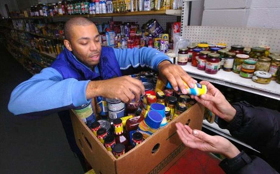 Photo/Alex von Kleydorff. James Atkinson, a staff member with Laurel House, fills some boxes with needed items off the shelves of the Lower Fairfield County Food Bank in Stamford.
