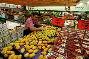 Roger Robles works on the mangos in the produce section at Fiesta Mart at 8130 Kirby Drive, Monday, May 23, 2016. Fiesta Mart is one of the top 10 private companies in the Chronicle 100 special section.
