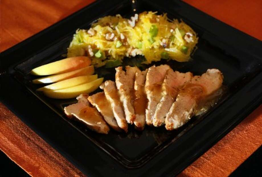 Butterflying the pork and microwaving the squash gets this pork tenderloin with apple and yellow spaghetti squash to the table in minutes. (MCT)