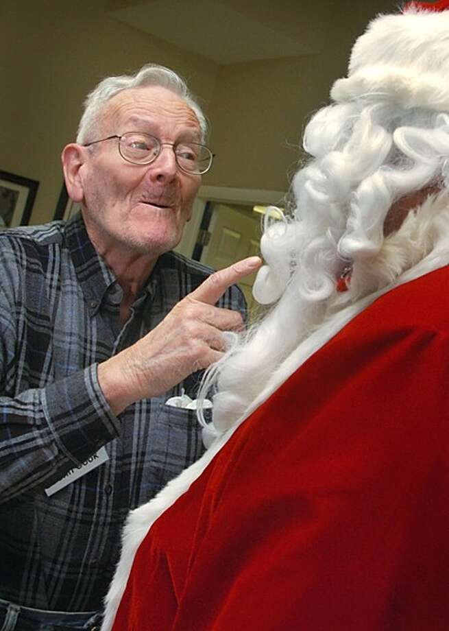 Elderhouse client John Cook has a word with santa, aka Norwalk police officer Joe Kubik, during a visit to Elderhouse sponsored by the Norwalk Police Department Tuesday. Hour photo / Erik Trautmann