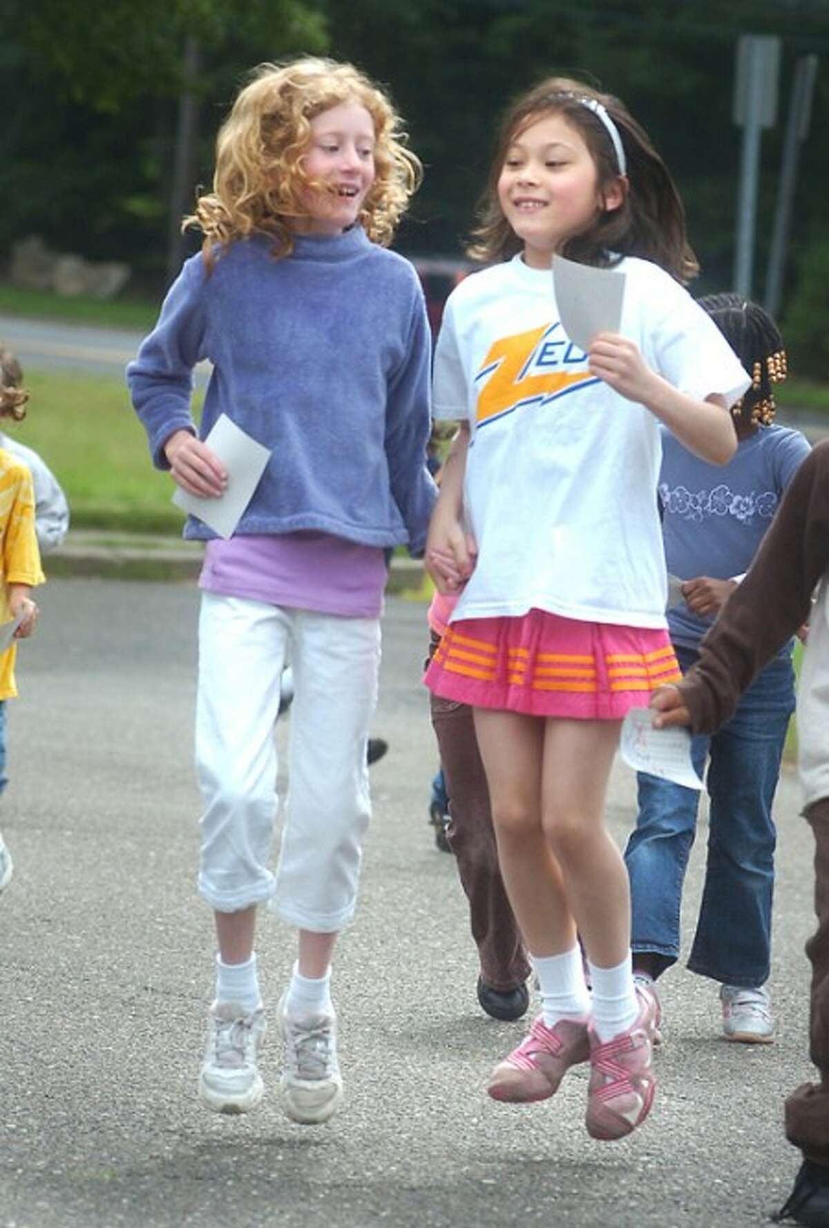 Photo/Alex von Kleydorff l-r Beatrice Phillips and Xuan Kusek try to hop their way trough a portion of the Fox Run School40 lap Walk a Thon sponsored by the PTO.