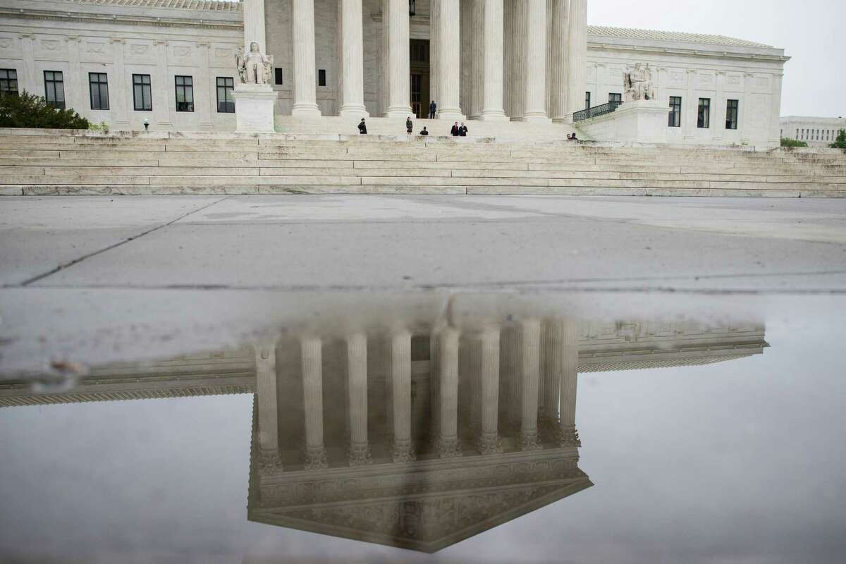 The U.S. Supreme Court is reflected in a puddle in Washington, May 2, 2016.