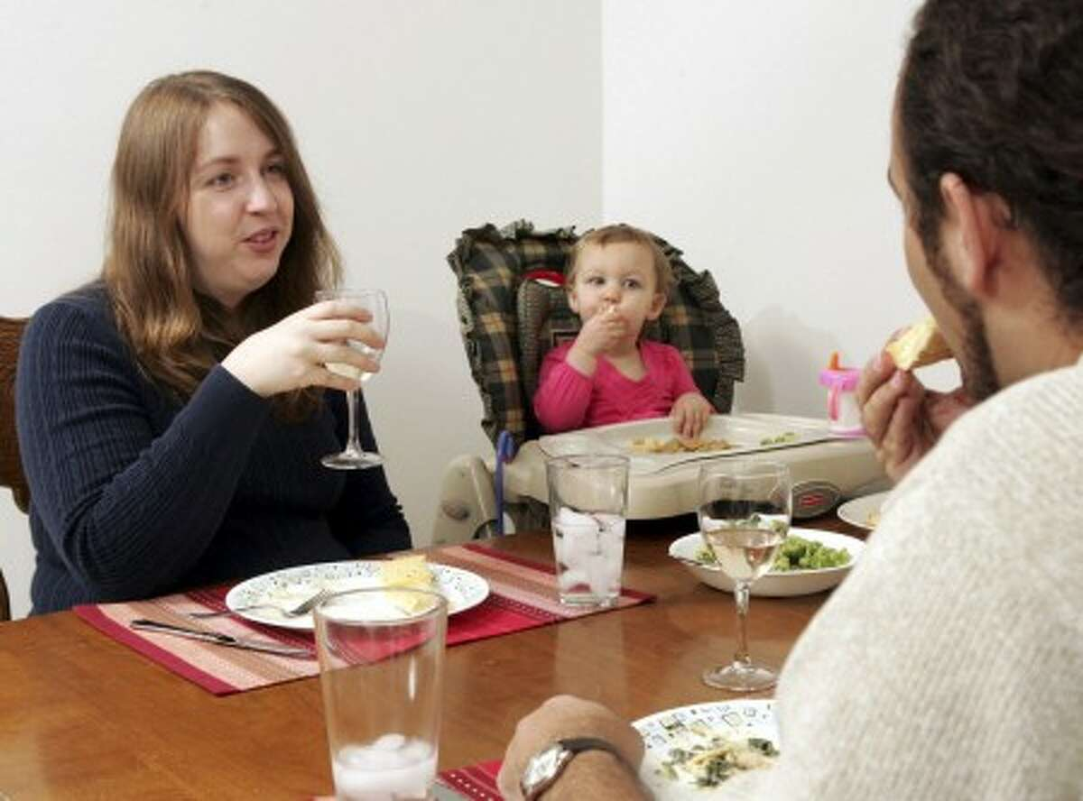 Christina McMenemy, left, is seen having dinner with her daughter Miranda, 18-months-old, center, and her husband Aaron at their residence in Grove City, Ohio, Monday, Sept. 17, 2008. McMenemy and her husband believe it is appropriate for them to have a glass of wine in front of their children so that their children know that beer or wine is OK for grown-ups. (AP Photo/Paul Vernon)