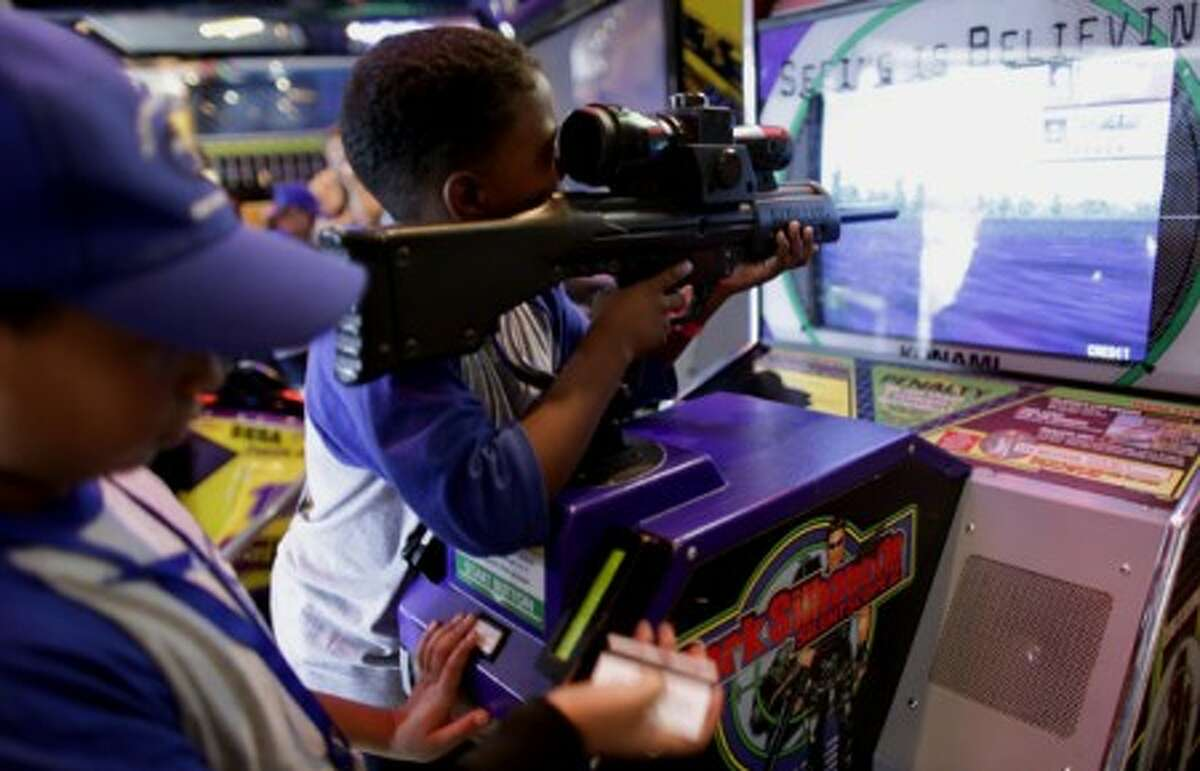 In this photo taken Sept. 2, 2009, a boy, using a toy weapon, plays a video game in Caracas. Venezuela''s National Assembly is on track to prohibit violent video games and toys. The proposed legislation, which received initial approval in September, is expected to get a final vote in the coming weeks. (AP Photo/Ariana Cubillos)