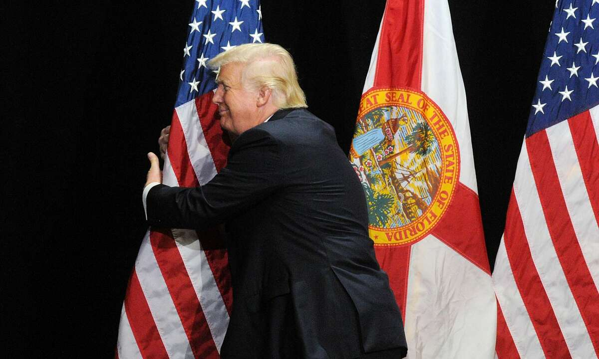TAMPA, FLORIDA - JUNE 11: Republican presidential candidate Donald Trump embraces the United States flag during a campaign rally at the Tampa Convention Center on June 11, 2016, in Tampa, Florida. Florida Gov. Rick Scott spoke at the rally and introduced Trump. (Photo by Gerardo Mora/Getty Images)