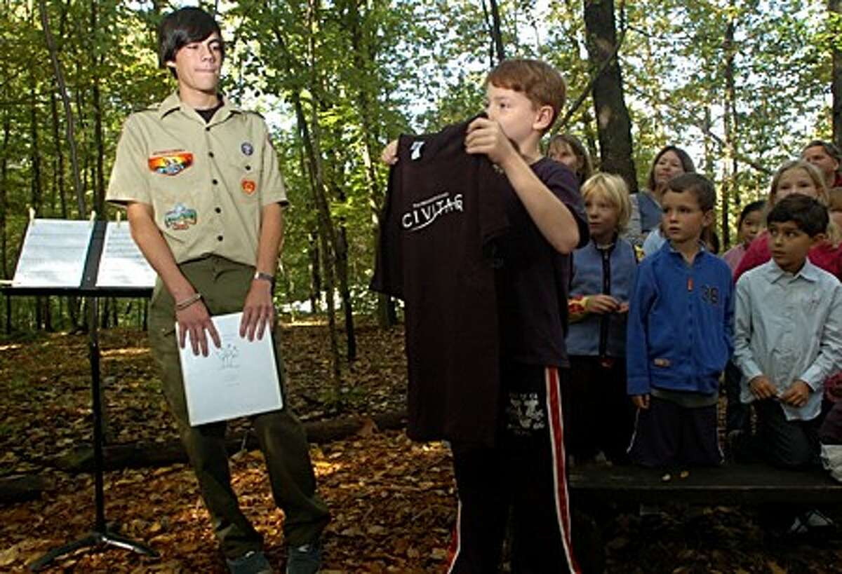 Montesorri School Upper School student Michael Kimball presents a gift to boy scout and former student Sebastian Van Eck during an outdoor ceremony honoring Van Eck who built trails and added other outdoor features to the property behind the school as part of his community service project to earn his Eagle Scout badge. Hour photo / Erik Trautmann