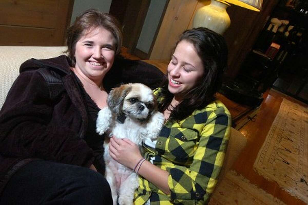 Photo/Alex von kleydorff. l-r Sisters Sarah and Julia Harris, share a moment with the family Shih Tzu, Tea Cup, on the couch in their Pound Ridge home.