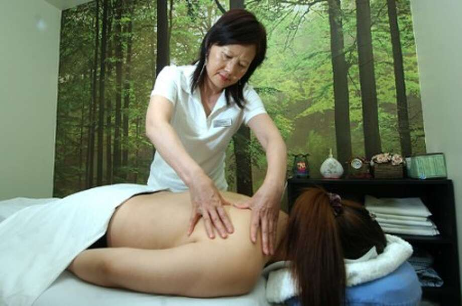 Photo/Alex von Kleydorff. Co- Owner Teresa Zhang gives a Deep Tissue massage to a client at Merritt Massage on Main Ave Norwalk.