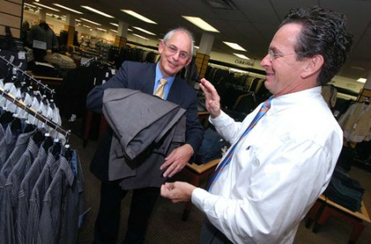 Photo/Alex von Kleydorff. Mayor Dan Malloy donates a suit to ARI President and CEO Matthew Reyher during a suit drive at Mens Warehouse in Stamford.