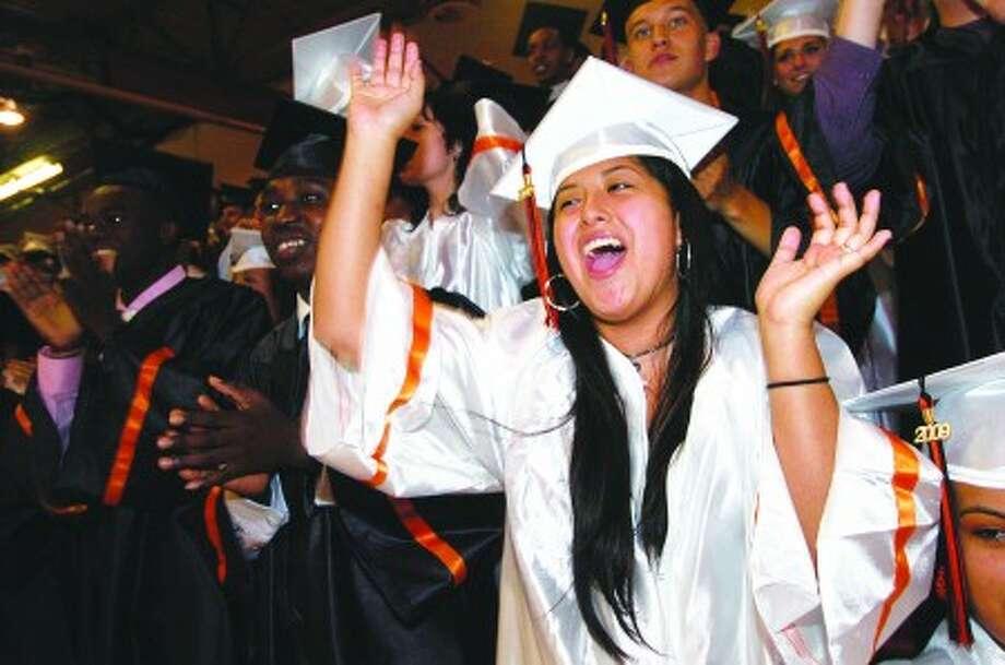 Photo/Alex von Kleydorff . Luvia Quiro shouts as the teaching staff proceeds to Stamford High School grauation.