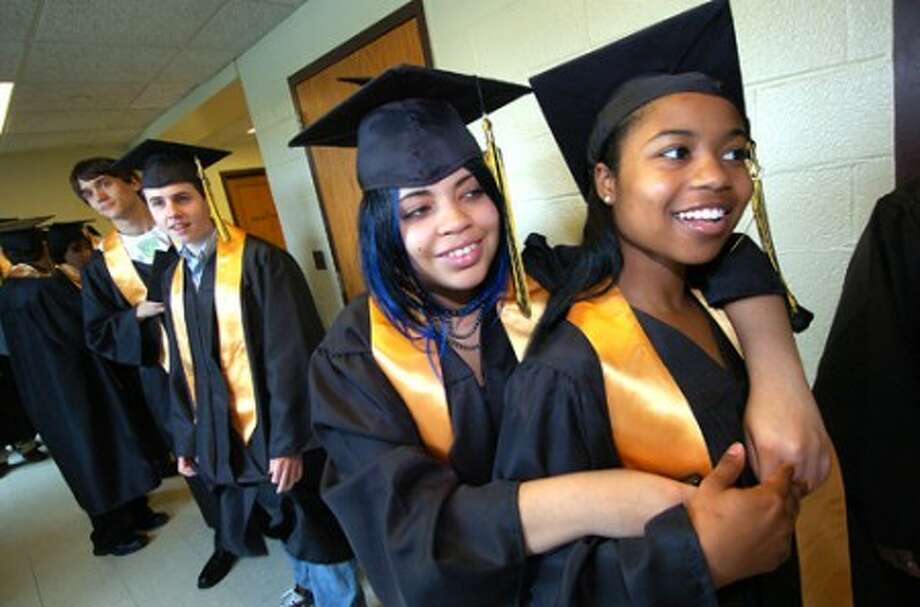 Photo/Alex von Kleydorff. Piniccea Hartwell and Minuette Griffin hold on to each other as they are about to graduate at AITE.