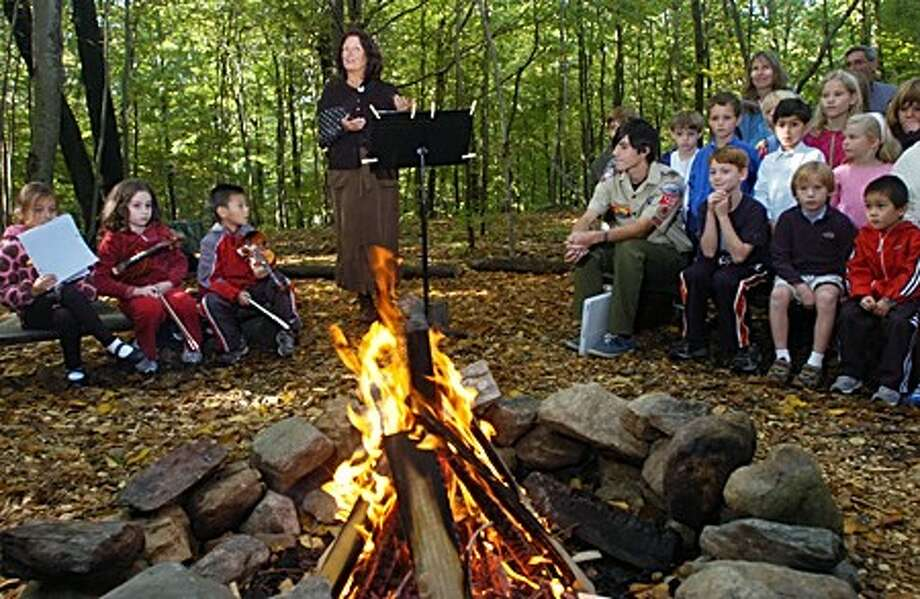 The head of the Montesorri School in Wilton, Mary Zeman, welcomes the students and guests Tuesday to an outdoor ceremony honoring boy scout and former student Sebastian Van Eck who built trails and added other outdoor features to the property behind the school as part of his community service project to earn his Eagle Scout badge. Hour photo / Erik Trautmann