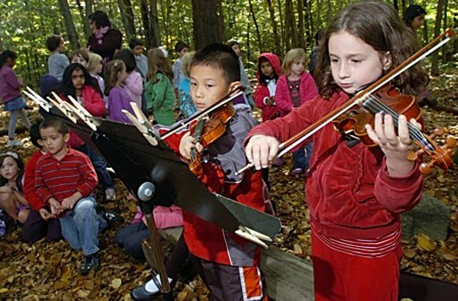 Montesorri School Lower School students Raymond Jia and Cecila Bersch play violin Tuesday during an outdoor ceremony honoring boy scout and former student Sebastian Van Eck who built trails and added other outdoor features to the property behind the school as part of his community service project to earn his Eagle Scout badge. Hour photo / Erik Trautmann