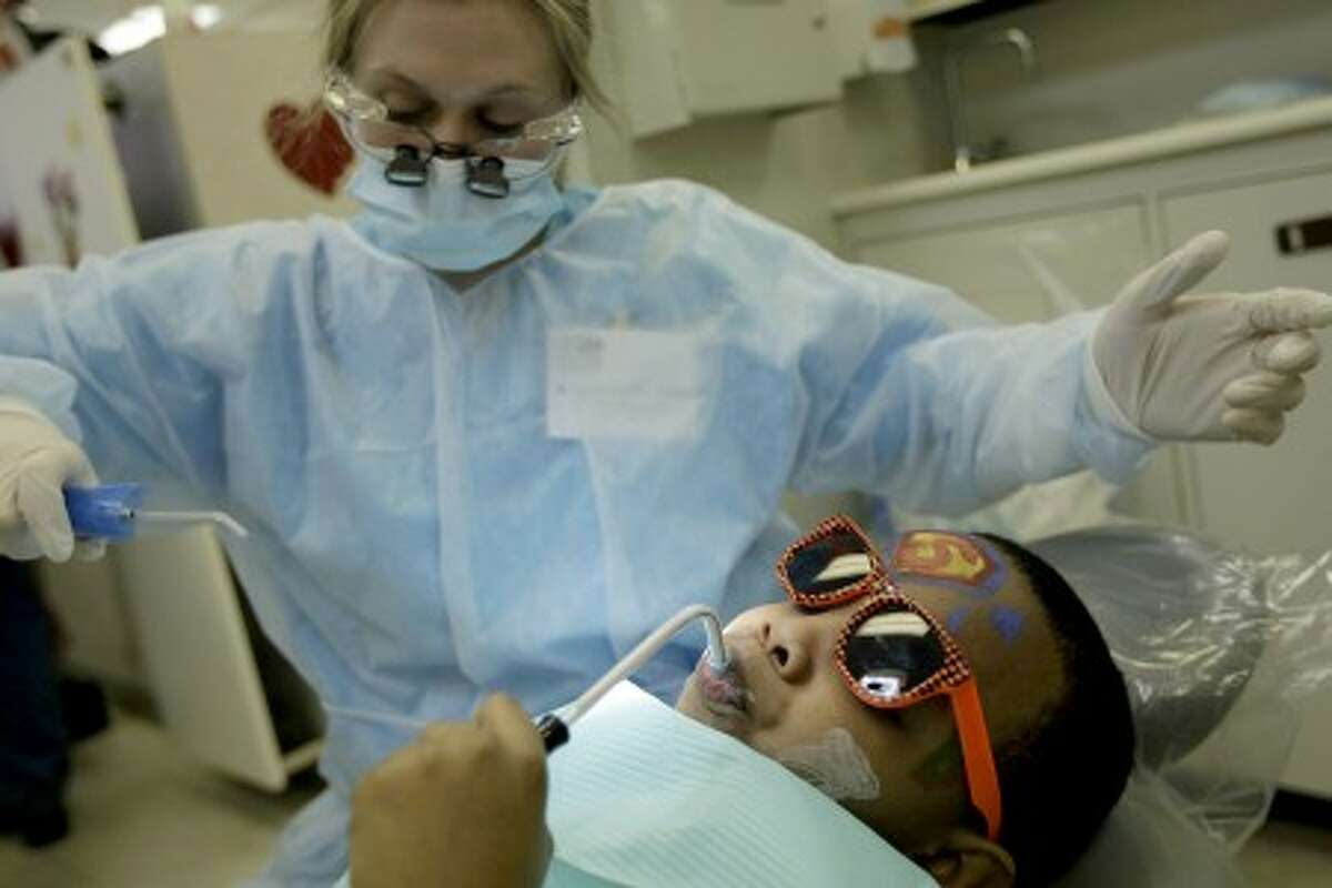 David Tingle, 8, gets his teeth cleaned for free by Stephanie Paoletto, a dental hygiene student. MCT photo