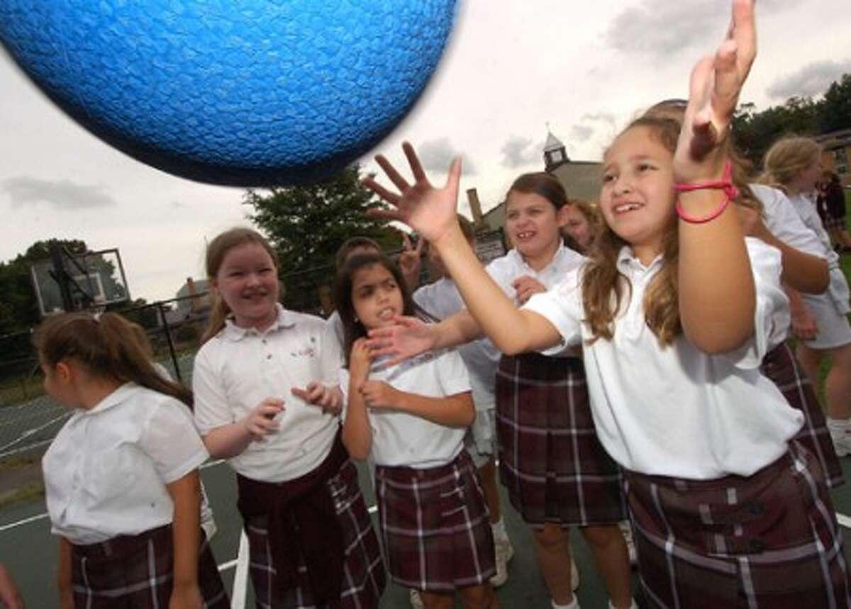 Photo/Alex von Kleydorff. 4th grader Stephanie Tancs plays with other classmates during recess at St Cecilia school in Stamford
