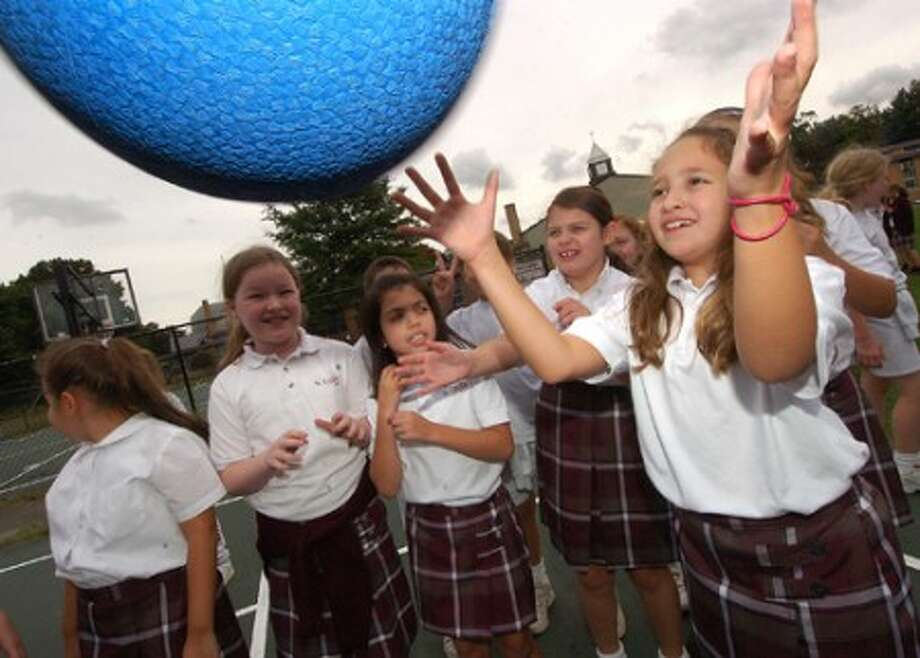 Photo/Alex von Kleydorff. 4th grader Stephanie Tancs plays with other classmates during recess at St Cecilia school in Stamford