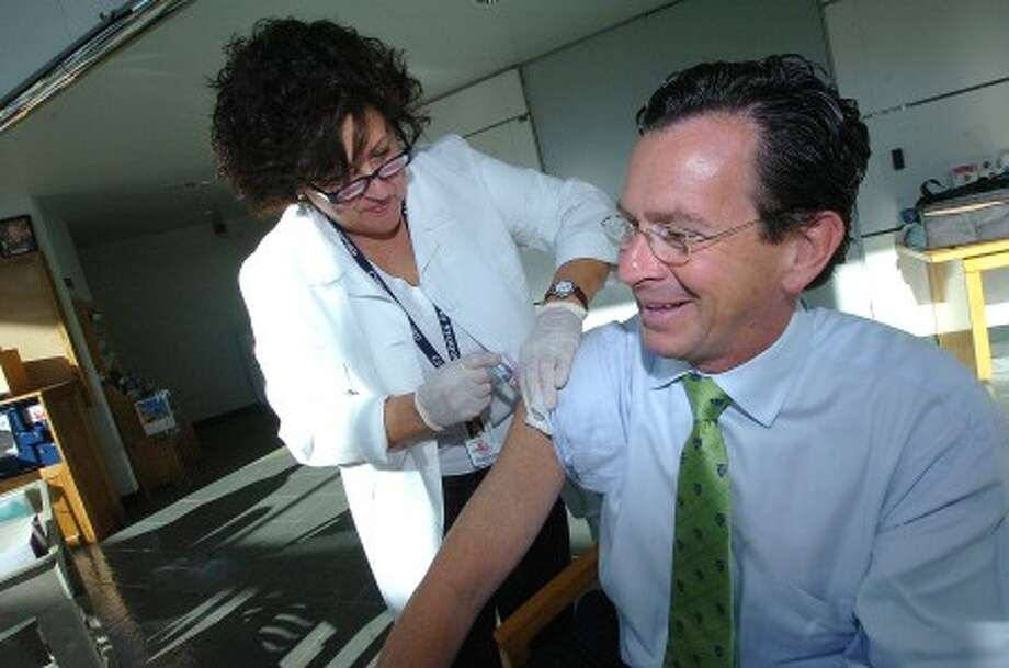 Photo/Alex von Kleydorff. Stamford health System R.N. Lynn Galgano gets Mayor Malloy immunized with a flu vacine at the Government center.