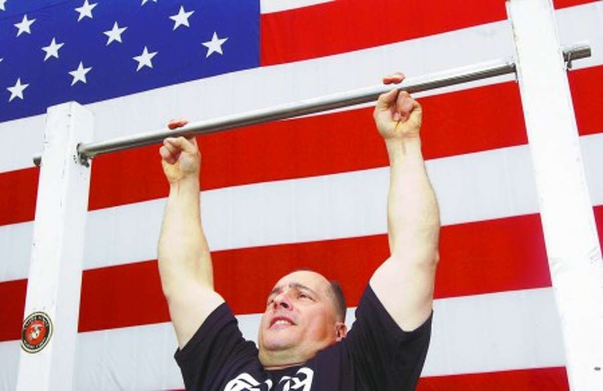 Ex-Marine and Stamford resident Alan Sharkeny is set the record for most two finger pull-ups accomplished in one hour in an event outside Tommy K''s Vitamins. Hour photo / Erik Trautmann