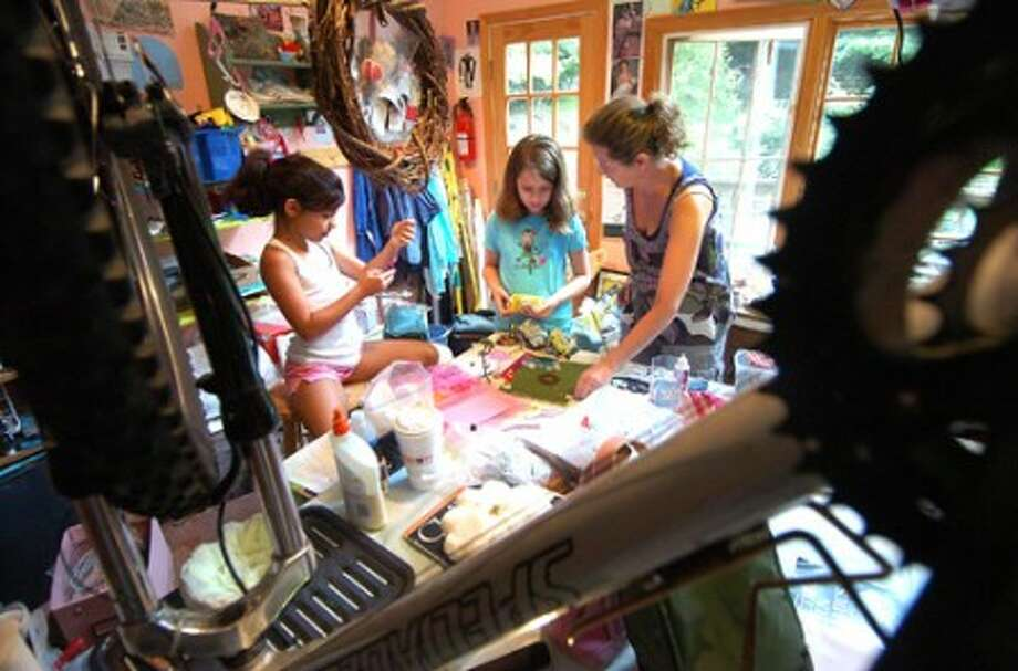Photo/Alex von Kleydorff. Instructor Emma Sutherland helps 8.5 yr old Christina Savas and 10yr old Ali Munro with their art projects in her home studio.