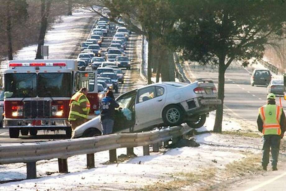 A car straddles the north and southbound guardrail on the Merrit Parkway at exit 25 in Stamford at around 2:00 on Monday afternoon/hour photo matthew vinci