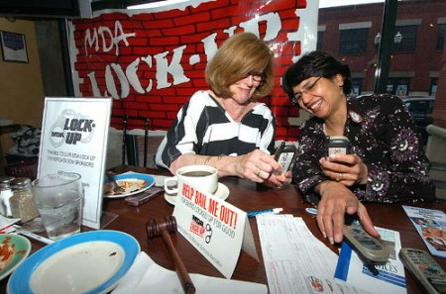 Photo/Alex von Kleydorff. l-r Jailbird Gail Malloy with Malloy Realty Group William Pitt Sothebys gets some dialing help from MDA program co-ordinator Anjali Desai to help her collect donations for her release from lock-Up at SBC Brewing Co in Stamford