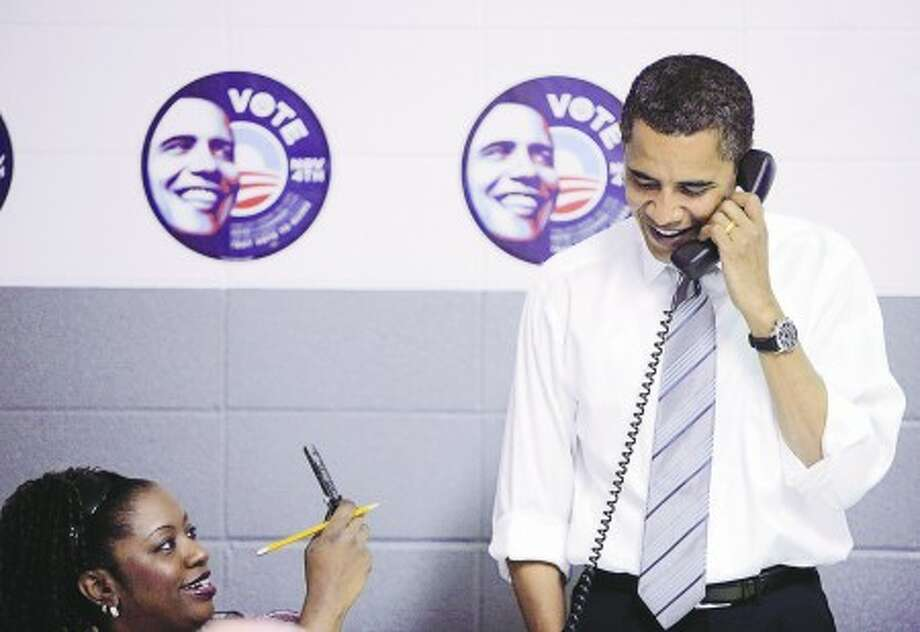 Democratic presidential candidate, Sen. Barack Obama, D-Ill., right, talks on the phone with a voter at the UAW Local 550 Union Hall in Indianapolis, Ind., Tuesday, Nov. 4, 2008. (AP Photo/Jae C. Hong)