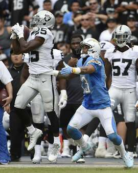 Oakland Raiders cornerback D.J. Hayden makes an interception as San Diego Chargers wide receiver Keenan Allen, right, looks on during the first half of an NFL football game Sunday, Oct. 25, 2015, in San Diego. (AP Photo/Denis Poroy)