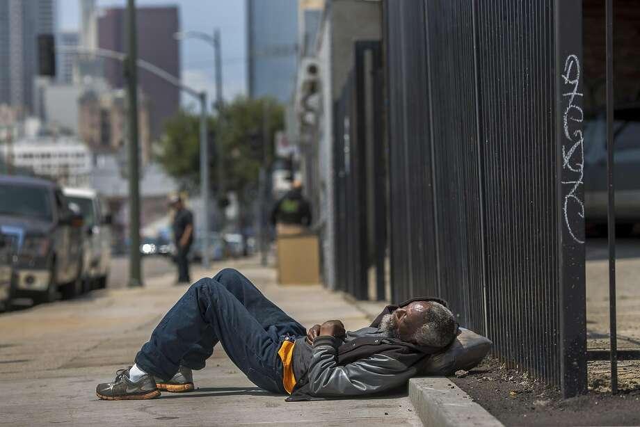 An elderly homeless man sleeps on a sidewalk on Skid Row in downtown Los Angeles, April 30, 2016.  Photo: MONICA ALMEIDA, NYT