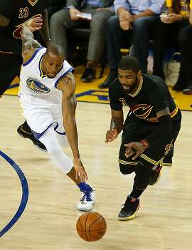 Golden State Warriors guard Andre Iguodala (left) and Cleveland Cavalier guard Kylie Irving scramble for a loose ball during the first quarter of game 5 of the NBA Finals on June 13, 2016 in Oakland, California.  / AFP PHOTO / Beck DiefenbachBECK DIEFENBACH/AFP/Getty Images