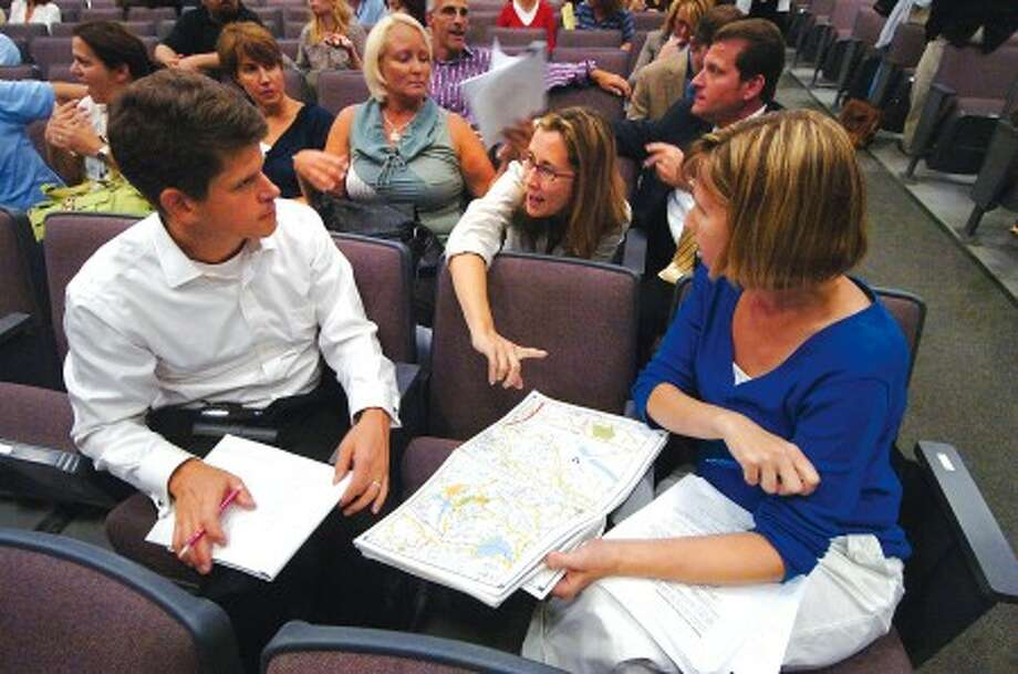 Photo/Alex von Kleydorff. l-R Peter Buckey, Deb Ehret and Janice Teske look over a road map of their Webbs Hill rd neigborhood for Roxbury school, and go through some notes as they prepare to speak at the re districting meeting at Cloonan middle school