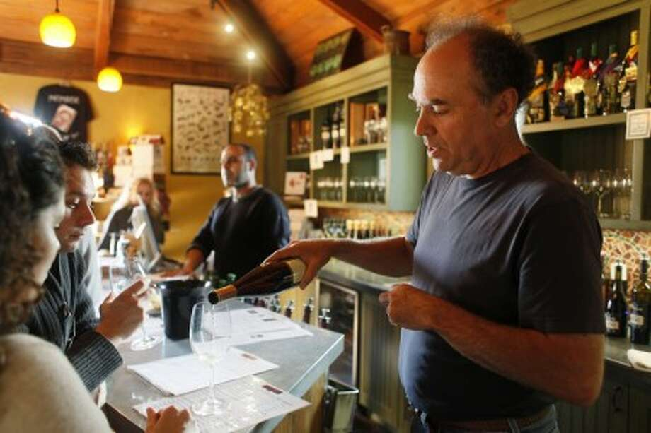 This photo taken Nov. 11, 2009 shows Ernie Weir, right, pouring wine in the tasting room at his Hagafen Cellars winery in Napa, Calif. The winery is one of the few that are kosher in the country.(AP Photo/Eric Risberg)