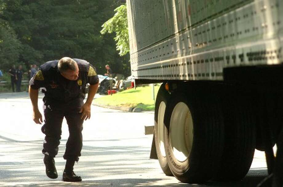 Photo/Alex von Kleydorff. Investigators with the Connecticut State Police Traffic Unit look at the rear wheel assembly of a tractor trailer involved in an accident with a passenger car on Rt 7 Monday Morning 080108