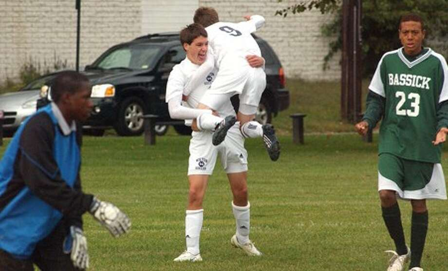 Wilton''s Evan Roux, left, hoists John Hoag into the air after Hoag scored Wilton''s first goal of the season in a 2-2 tie with Bassick on Thursday afternoon. (Photo by John Nash/Wilton Villager)