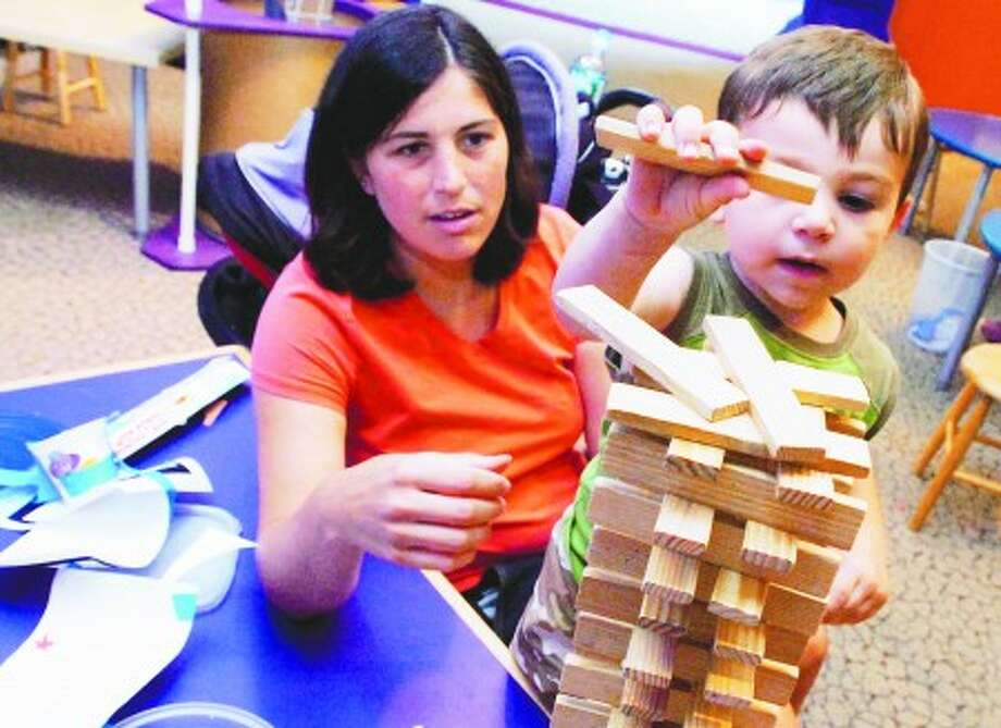 Two year old Dominic Durante tops off his wood buliding with help from his mom Amanda at the invention convention activity at the Stepping Stones Museum For Children on Tuesday/hour photo matthew vinci