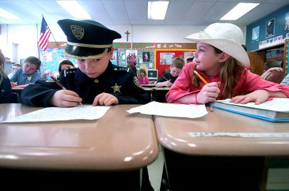 Photo/Alex von Kleydorff.l 8yr old Dylan Ehlers dessed as a police officer, works on a writing project with Erin Dellisanti as an Olympic Equestrian in Patty O''Shea''s Our Lady of Fatima 3rd grade class during hero day.