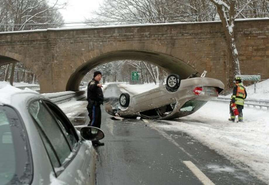 Police officers and firemen respond to an accident that happened near exit 41 on the Merritt Parkway in Westport Monday morning during the snow storm. Hour Photo / Danielle Robinson