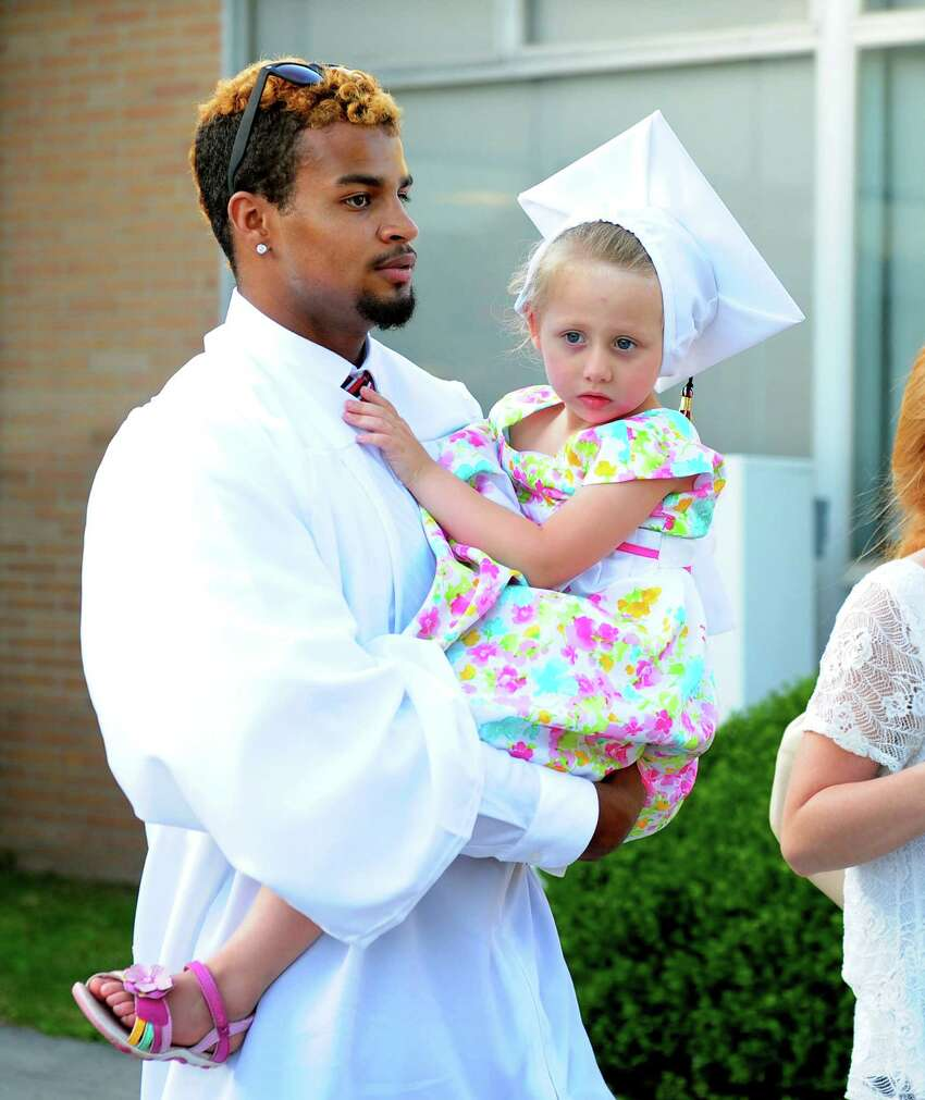 Graduate David Abrahams carries his niece Hailie, 4, as she wears his cap after Fairfield Warde High School's Class of 2016 Commencement Exercises in Fairfield, Conn., on Thursday June 16, 2016.