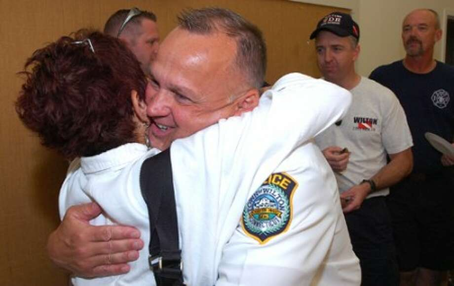 Photo/Alex von Kleydorff. Lauren Hughes gives a hug to Wilton Police Chief Ed Kulhawik at a party for his retirement at Town Hall Tuesday.