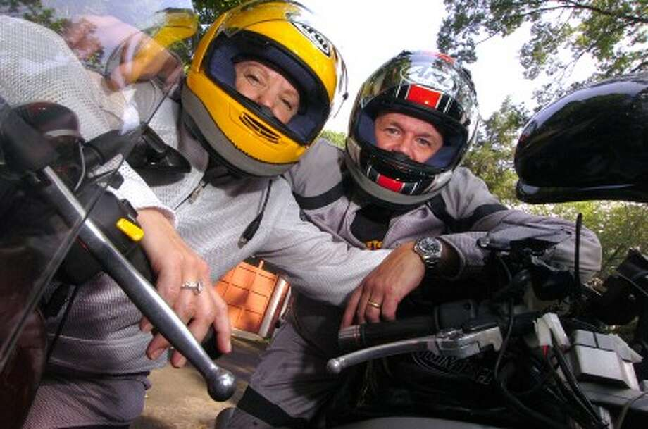 Photo/Alex von Kleydorff. Moira and Kevin Craw suited up on the motorcycles they toured almost 6000 miles on, throughout America this summer.