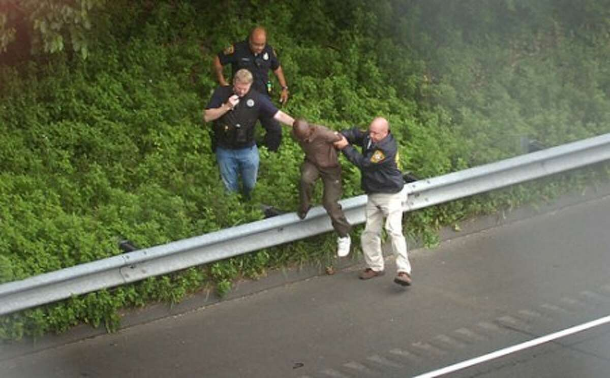 Photo/Alex von Kleydorff. Norwalk Police apprehend Gilbert Orlando from the woods along I95 northbound at exit 15, in connection for a double homicide earlier on Couch st.