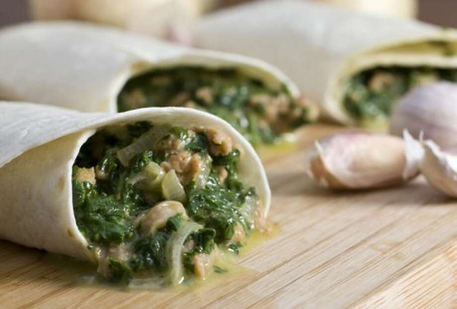 Flexible and filling Spicy Sausage Wraps with Golden Onions and Spinach are an easy and economical complete meal. (AP Photo/Larry Crowe)