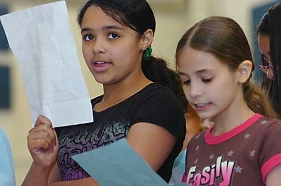 Brookside 5th graders, Jasmine Banks and Denisse Arzola perform a song with their class called The Phineas and Ferd re-mix which was written by fellow student Olivia Rosado at the poetry slam held at the school on Wednesday/hour photo matthew vinci